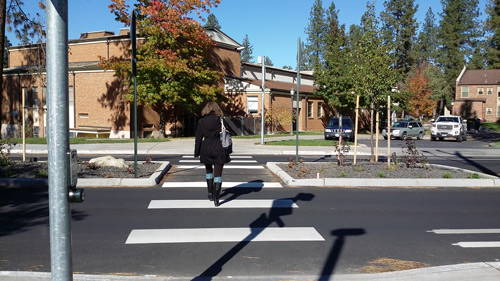 Crosswalk in North Spokane with woman using it to cross the street.